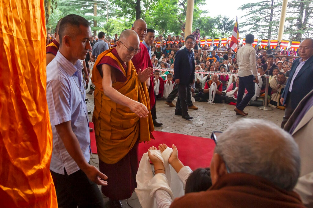 Tibetan spiritual leader the Dalai Lama, in yellow robe, greets a devotee as he arrives at the Tsuglakhang temple in Dharamshala, Friday, July 5, 2019. (AP Photo/Ashwini Bhatia)