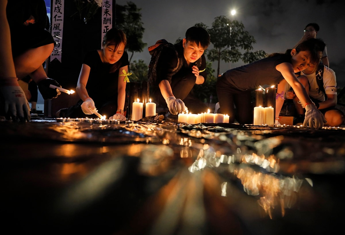 People light candles during a vigil to mourn the recent suicide of a woman due to the government's policy on the extradition bill, in Hong Kong. A vigil is being held in Hong Kong for a woman who fell to her death this week, one of three apparent suicides linked to ongoing protests over fears that freedoms are being eroded in this semi-autonomous Chinese territory. (AP Photo/Vincent Yu, File)