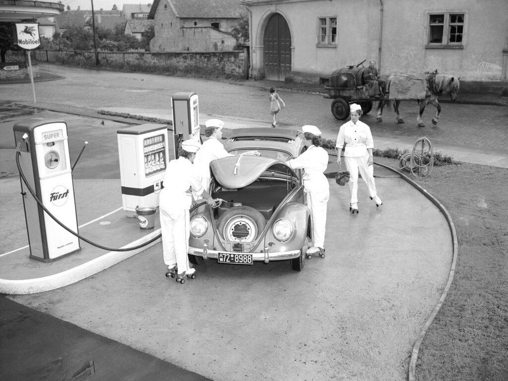 In this Aug. 23, 1954 file photo, four female employees tend to a Volkswagen at a gas station in Deidesheim, near Kaiserslautern, Germany. Volkswagen is halting production of the last version of its Beetle model in July 2019 at its plant in Puebla, Mexico, the end of the road for a vehicle that has symbolized many things over a history spanning eight decades since 1938.(AP Photo/Albert Riethausen, File)