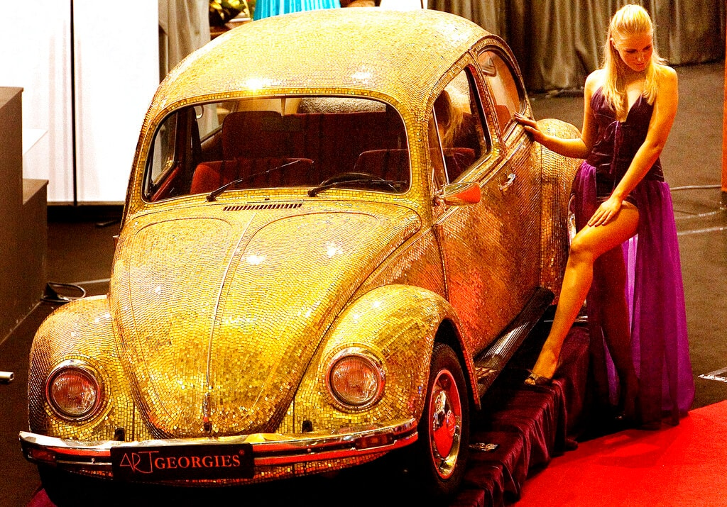 In this Dec. 8 2007 file photo, a model poses next to a 1968 Volkswagen Beetle covered in tiles made of a blend of 18 karat gold and glass at the annual Luxury Show in Bucharest, Romania. The car is functional and on sale for 60,000 euros, $88,000. However it is not street legal in Romania because of the nature of its paint. Volkswagen is halting production of the last version of its Beetle model in July 2019 at its plant in Puebla, Mexico, the end of the road for a vehicle that has symbolized many things over a history spanning eight decades since 1938.(AP Photo/Vadim Ghirda, file)