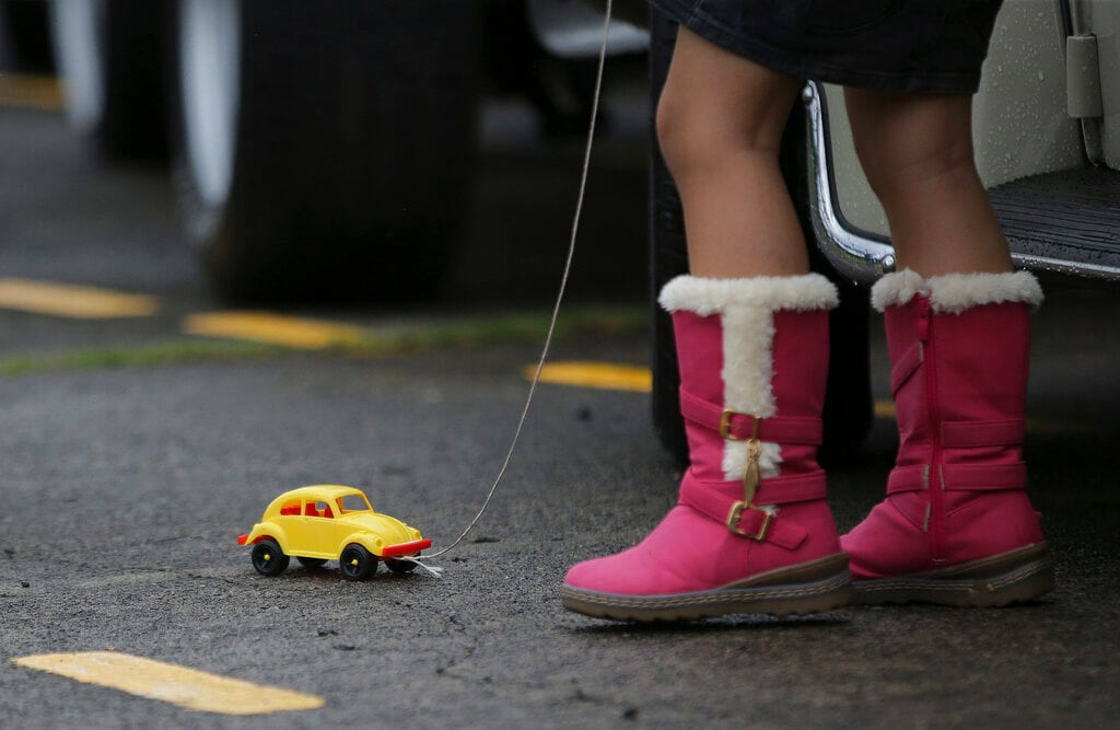 In this June 22, 2014, file photo a Filipino girl plays with a toy Volkswagen Beetle as she joins activities to celebrate World Volkswagen Day at Camp Aguinaldo in suburban Quezon city, north of Manila, Philippines. Volkswagen is halting production of the last version of its Beetle model in July 2019 at its plant in Puebla, Mexico, the end of the road for a vehicle that has symbolized many things over a history spanning eight decades since 1938. (AP Photo/Aaron Favila, File)