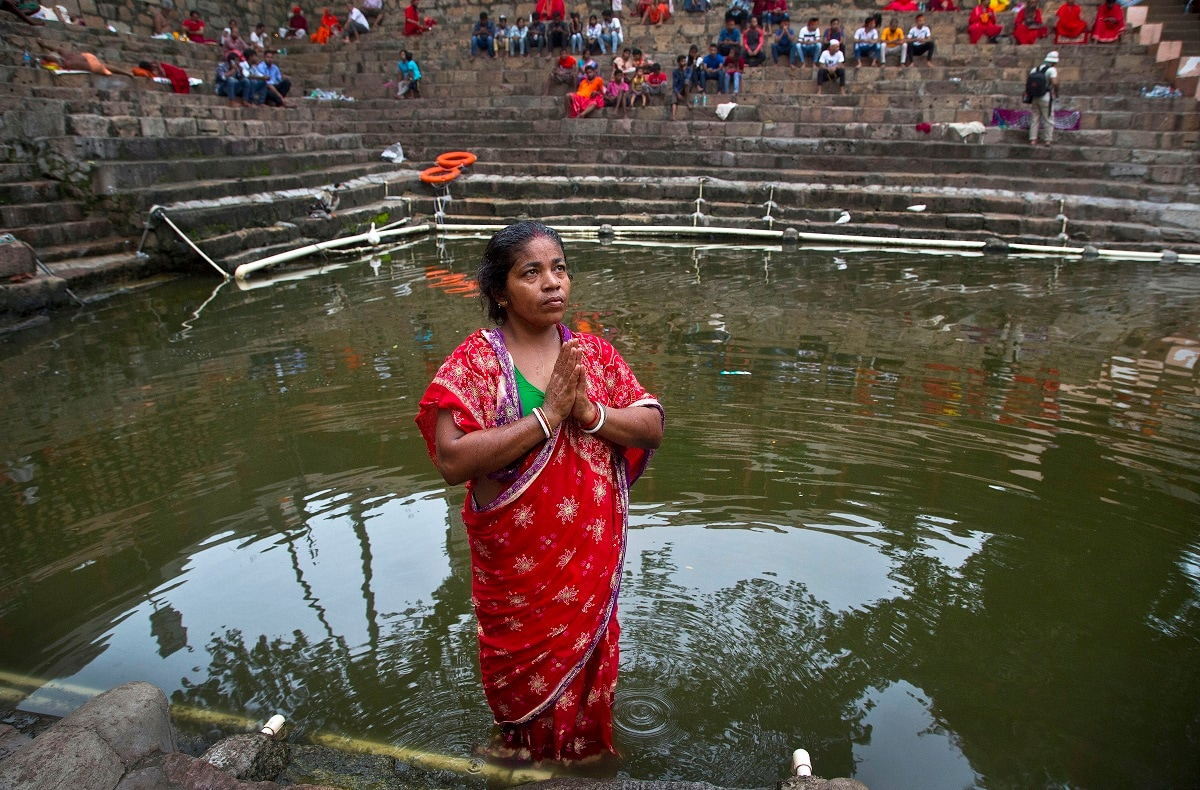 Monika Deb Nath, 45, offers prayers before taking a dip in the temple pond at the Kamakhya temple during the Ambubachi festival in Gauhati, India. Monika, 45, and her husband have visited the Kamakhya temple four years in a row for the annual Ambubachi festival, praying for a miracle to heal their son from cerebral palsy, which has left him with almost no control over his own body. The temple is presided over by the goddess Kamakhya, the most important goddess of tantric worship, an esoteric form of Hinduism. (AP Photo/Anupam Nath)