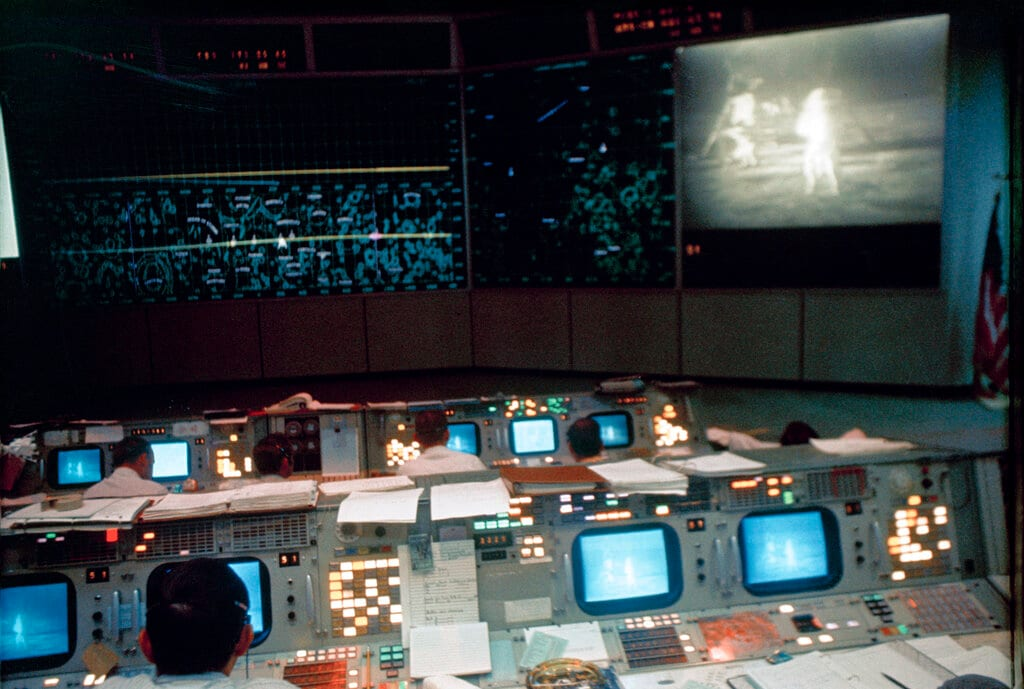 In this July 20, 1969 photo made available by NASA, flight controllers work in the Mission Operations Control Room in the Mission Control Center during the Apollo 11 lunar extravehicular activity. The television monitor shows astronauts Neil Armstrong and Buzz Aldrin on the surface of the moon. (NASA via AP)