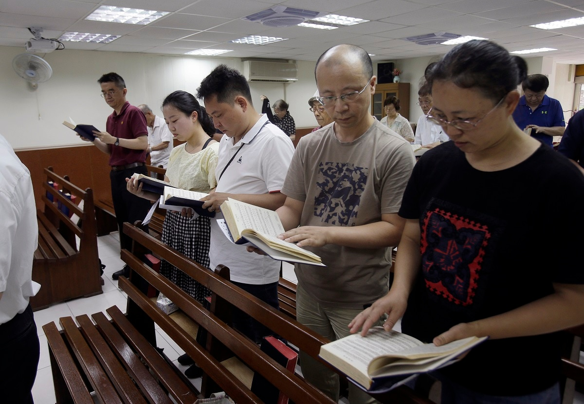 Ren Dejun, Liao Qiang, Peng Ran and Ren Ruiting follow a hymn book during service at a church in Taipei, Taiwan. The Sunday service this week at an unassuming church in Taiwan was especially moving for one man, Liao Qiang. It was the first time he had worshipped publicly since authorities shut down his church in China seven months ago. (AP Photo/Chiang Ying-ying, File)