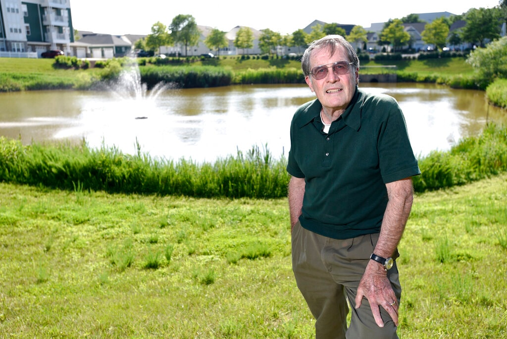Clancy Hatleberg, who was the first person to interact with the Apollo 11 crew when they returned to earth from the moon on July 24, 1969, stands near a pond outside his home Friday, July 11, 2019 in Laurel, Md. He was 25 at the time of the historic mission and fresh from an underwater demolition team rotation in Vietnam. (AP Photo/Steve Ruark)