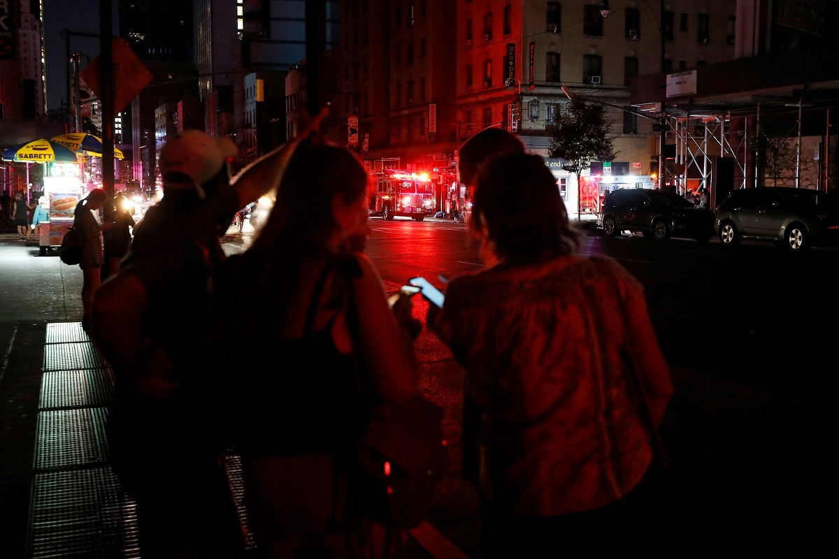 Pedestrians look at their cellphones during a power outage in midtown Manhattan in New York. Authorities were scrambling to restore electricity to Manhattan following a power outage that knocked out Times Square's towering electronic screens and darkened marquees in the theater district and left businesses without electricity, elevators stuck and subway cars stalled. (AP Photo/Michael Owens)