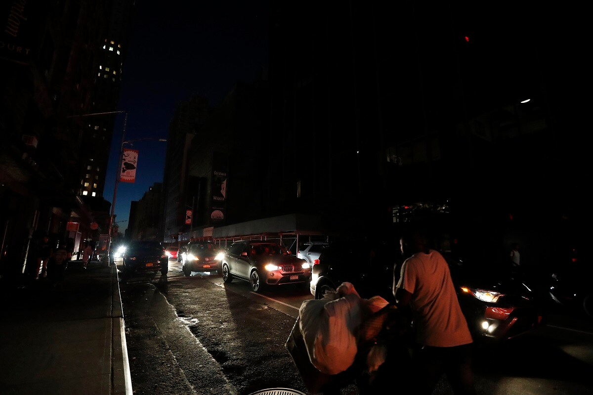 A man makes his way through a dark Times Square during a power outage. (AP Photo/Michael Owens)