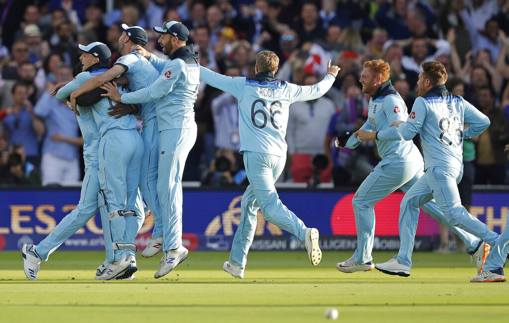 England players mob Jofra Archer after he bowled the super over to win the Cricket World Cup final match between England and New Zealand at Lord's cricket ground in London, Sunday, July 14, 2019. (AP Photo/Matt Dunham)