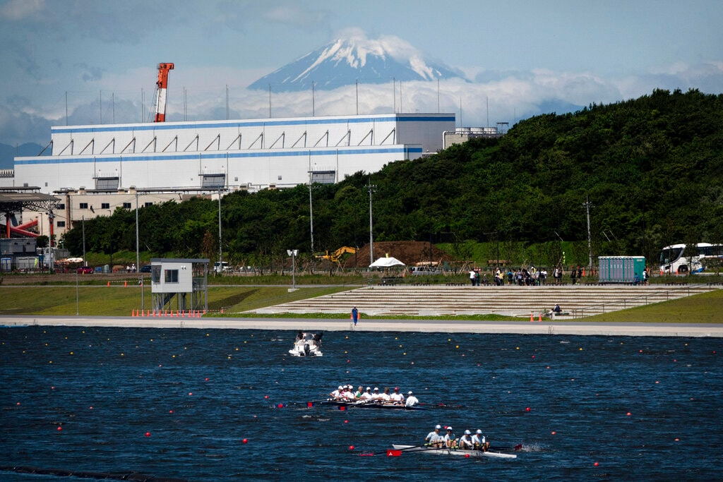 Rowers prepare for a test run at the Sea Forest Waterway, a venue for rowing at the Tokyo 2020 Olympics, as Mount Fuji is visible in the distance in Tokyo. Scandals and rising costs have not deterred interest in Japan in the Tokyo Olympic. They open in a year with unprecedented ticket demand. (AP Photo/Jae C. Hong, File)