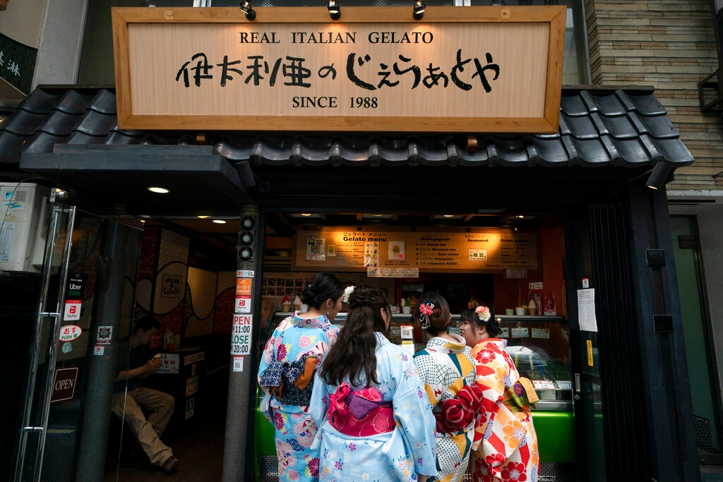 Wearing rental kimonos, tourists visiting from Hong Kong order gelato after their visit to Sensoji Temple in the Taito district of Tokyo, June 3, 2019. (AP Photo/Jae C. Hong)