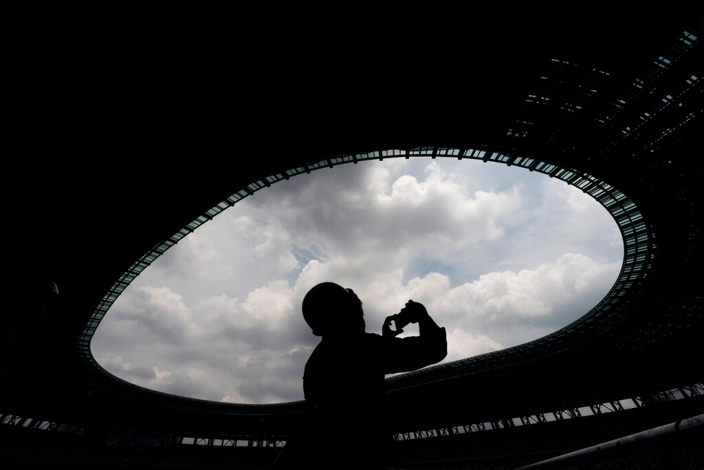 A journalist is silhouetted while taking photos of New National Stadium in Tokyo, July 3, 2019. The stadium will host the opening and closing ceremonies at the 2020 Summer Olympics. (AP Photo/Jae C. Hong)