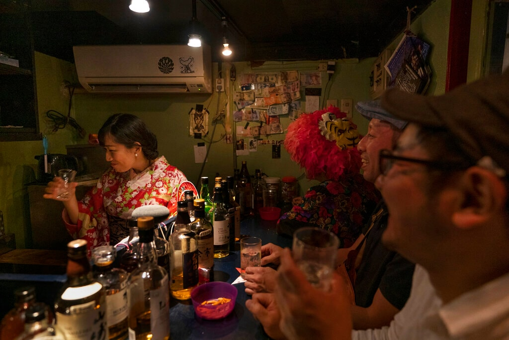 Bar owner Marie Yoshida, left, drinks with customers in her bar that seats eight people in Golden Gai, a bar district in the Shinjuku neighborhood of Tokyo, June 1, 2019. (AP Photo/Jae C. Hong)
