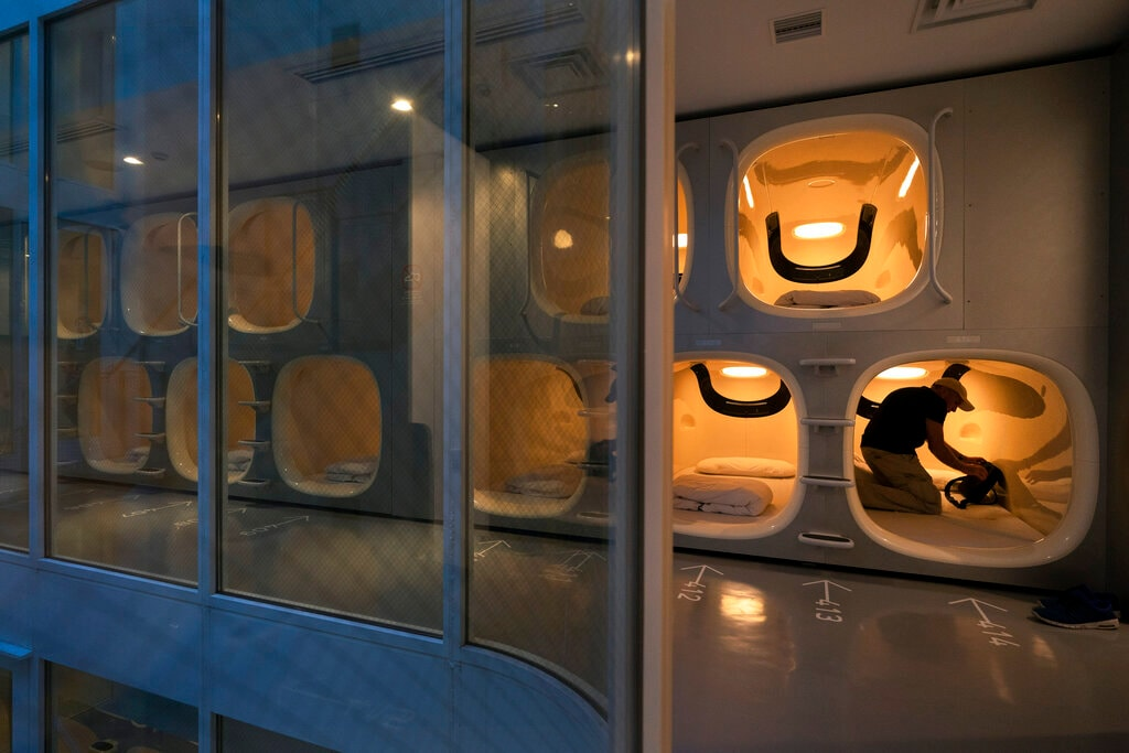 Laurent Colin, a 46-year-old tourist visiting from Australia, settles into his pod at the 9H capsule hotel in the Chiyoda district of Tokyo, May 30, 2019. (AP Photo/Jae C. Hong)