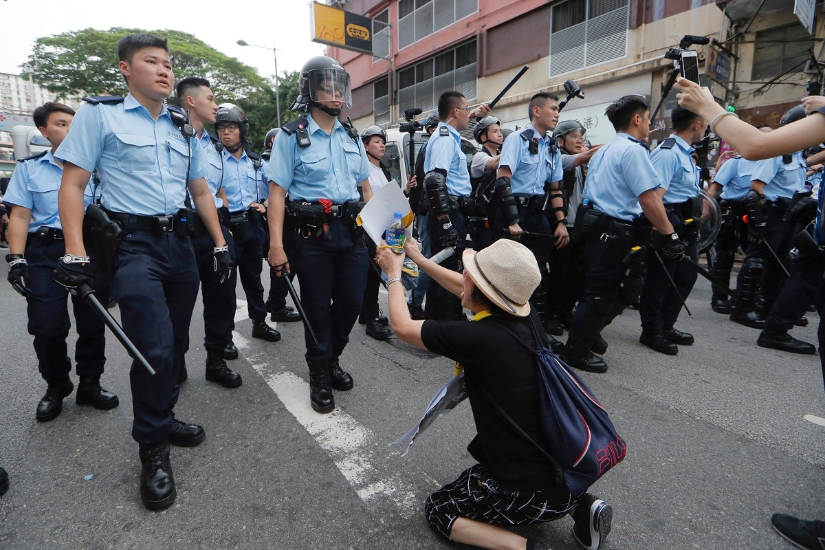 A supporter begs police officer not to attack protesters in Hong Kong. Several thousand people marched in Hong Kong on Saturday against traders from mainland China in what is fast becoming a summer of unrest in the semi-autonomous Chinese territory. (AP Photo/Kin Cheung, File)