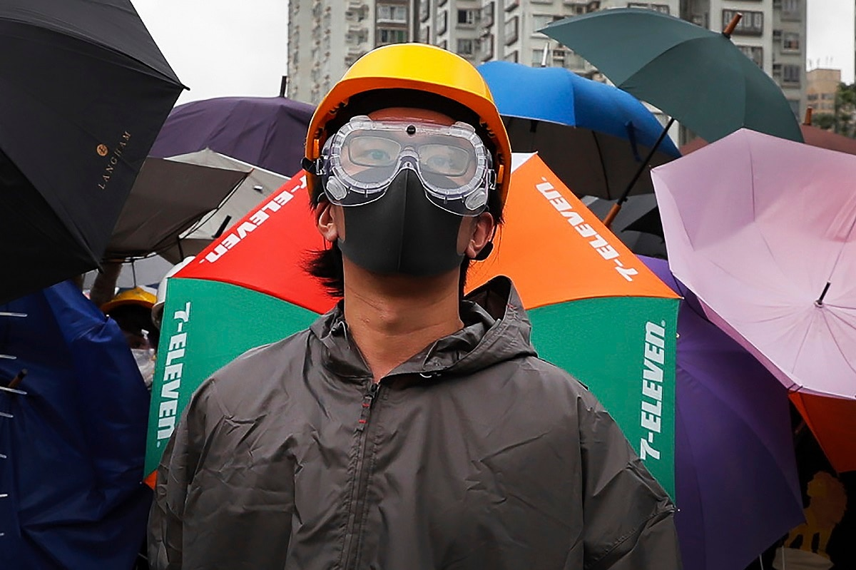 A protester with protection gear stands watch as they use umbrellas and steel barricades to block a road during a march through Sha Tin District in Hong Kong. Opponents of a proposed Hong Kong extradition law have begun a protest march, adding to an outpouring of complaints the territory's pro-Beijing government is eroding its freedoms and autonomy. (AP Photo/Kin Cheung, File)