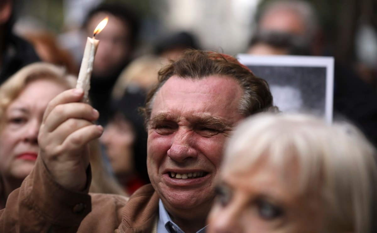 A man cries as he holds up a candle on the 25th anniversary of the bombing of the AMIA Jewish centre that killed 85 people in Buenos Aires, Argentina. (AP Photo/Natacha Pisarenko)