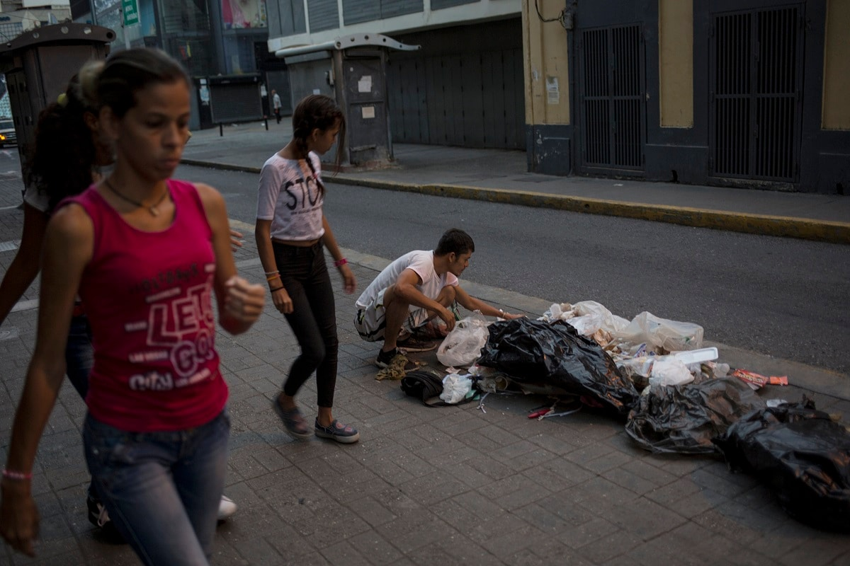 Kevin Gonzalez searches for food in the trash, on a sidewalk in Caracas, Venezuela. (AP Photo/Rodrigo Abd)