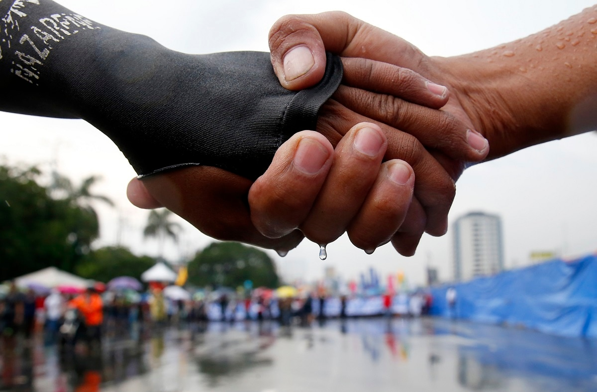Protesters link hands as they lead the march under the rain towards the Philippine Congress to protest the 4th State of the Nation (SONA) address by President Rodrigo Duterte in suburban Quezon city, northeast of Manila, Philippines. Duterte is facing criticisms about his alleged closeness with China as well as the thousands of killings in his so-called war on drugs. (AP Photo/Bullit Marquez)