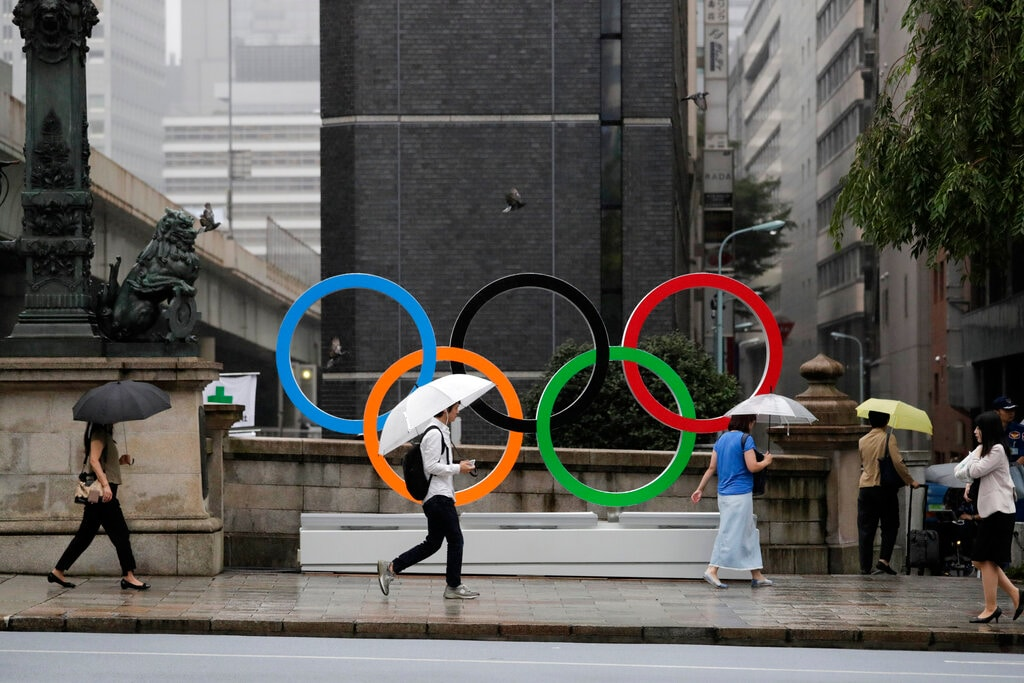 Commuters walk past the Olympic Rings Tuesday, July 23, 2019, in Tokyo. (AP Photo/Jae C. Hong)