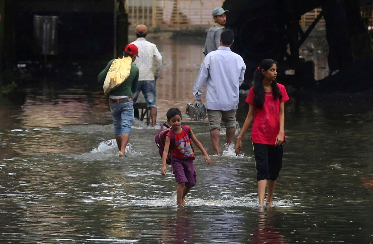 People walk past a waterlogged street after rainfall in Mumbai. Office-goers and students alike were hit due to crawling traffic, besides suburban trains running late by 15-25 minutes on the Western Railway and Central Railway. (AP Photo/Rafiq Maqbool)