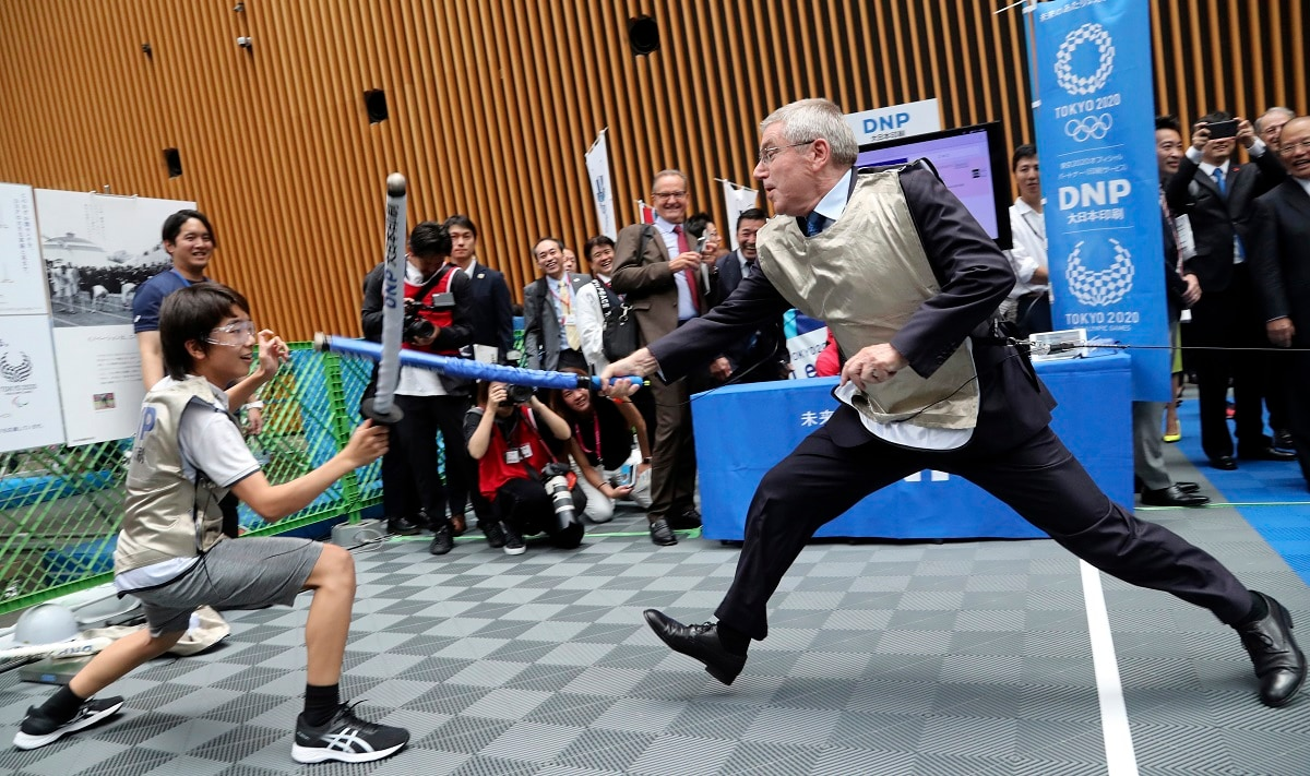 IOC President Thomas Bach, right, demonstrates fencing with Japanese junior high school student Yui Hashimoto during an Olympic Games Tokyo 2020 One year to Go ceremony event in Tokyo. Bach is a former Olympic fencer and won a team gold medal at the 1976 Montreal Games. (AP Photo/Koji Sasahara, Pool)