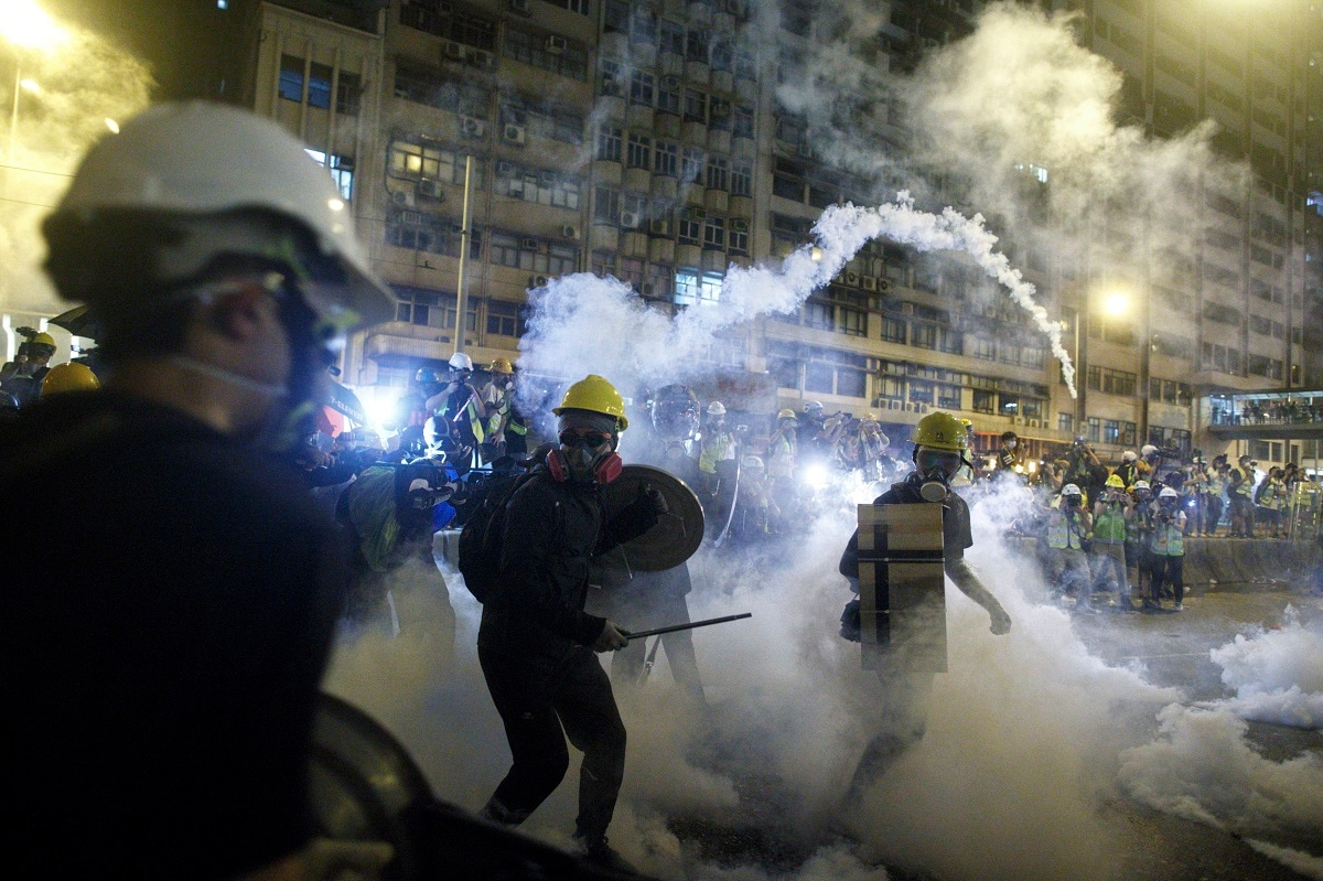 Protesters react to tear gas during a confrontation with riot police in Hong Kong. Hong Kong police launched tear gas at protesters Sunday after a massive pro-democracy march continued late into the evening. The action was the latest confrontation between police and demonstrators who have taken to the streets to protest an extradition bill and call for electoral reforms in the Chinese territory. (Eric Tsang/HK01 via AP)
