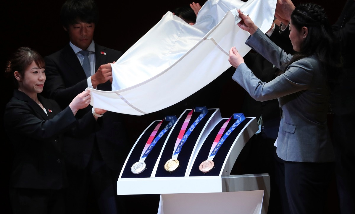 In this July 24, 2019, photo, Tokyo 2020 Olympic medals are unveiled during the One Year to Go Olympic ceremony in Tokyo. Gold, silver, and bronze Olympic medals were to get their first public viewing on Wednesday as Tokyo organizers marked exactly a year until the games open. (AP Photo/Koji Sasahara)