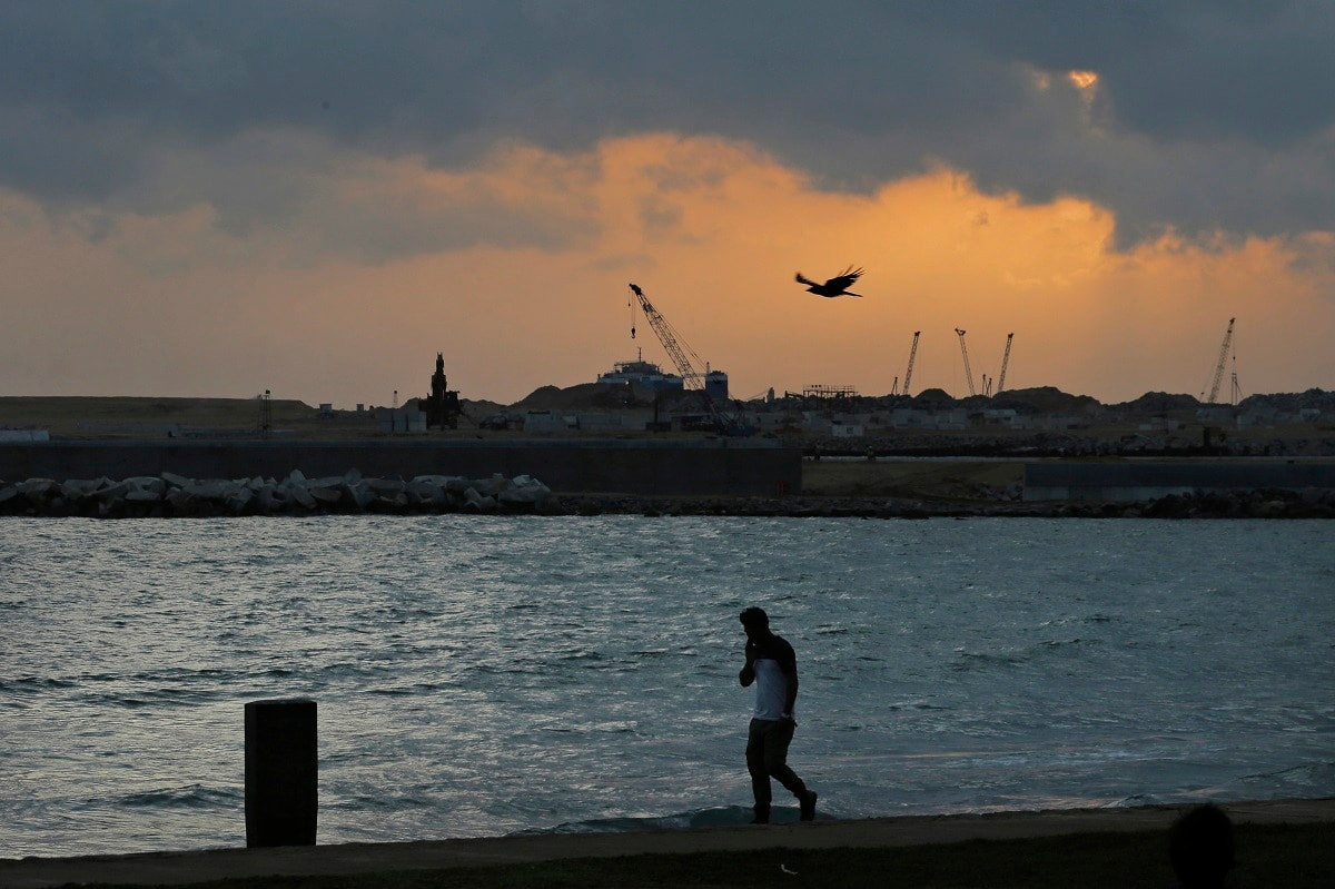 A Sri Lankan walks by Galle Face, in front of the Chinese-funded sea reclamation project in Colombo, Sri Lanka. Shocks from deadly suicide bombings on Easter Day in Sri Lanka are reverberating throughout its economy in the worst crisis since the South Asian island nation's civil war ended in 2009. The blasts have devastated Sri Lanka's vital tourism industry, source of jobs for many, and hindering foreign investment. (AP Photo/Eranga Jayawardena)