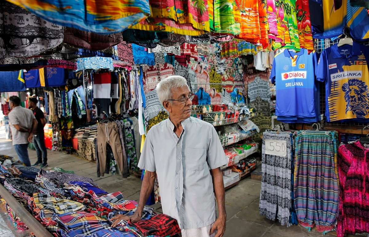 """Sri Lankan trader Ranepura Hewage Jayasena, 76, waits for customers at a shop selling mementoes in Colombo. """"Almost 100 percent of my business is gone. There are days without a single sale,"""" said Jayasena, looking grief-stricken as he went through the previous days accounts. """"We had a war that raged for years, but we had good business. Bombs exploded in Colombo city itself, but that did not affect our business,"""" he said. """"This is the worst period I have seen in my life."""" (AP Photo/Eranga Jayawardena)"""