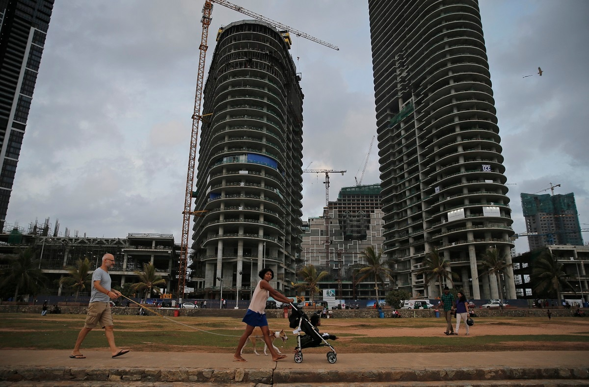 People walk past construction sites built with foreign investment in the Galle Face sea promenade in Colombo. (AP Photo/Eranga Jayawardena)