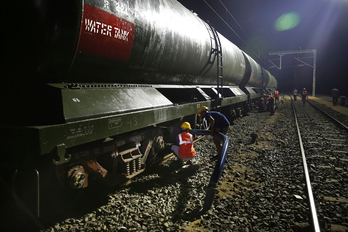 Workers attach a blue pipe to decant drinking water from a train at Villivakkam railway station. (AP Photo/Manish Swarup)