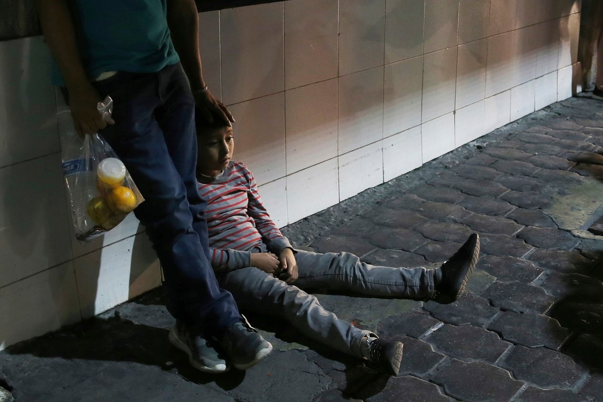 A migrant child and his father stay together after being bused by Mexican migration authorities from Nuevo Laredo to Monterrey, Mexico. Unlike asylum seekers who wait in line, often for months, to file claims in the US and then return to the Mexican border cities where they were before, all those taken to Monterrey who spoke with AP said they had crossed illegally and spent several days in US detention centres before being returned with a court date. (AP Photo/Marco Ugarte)