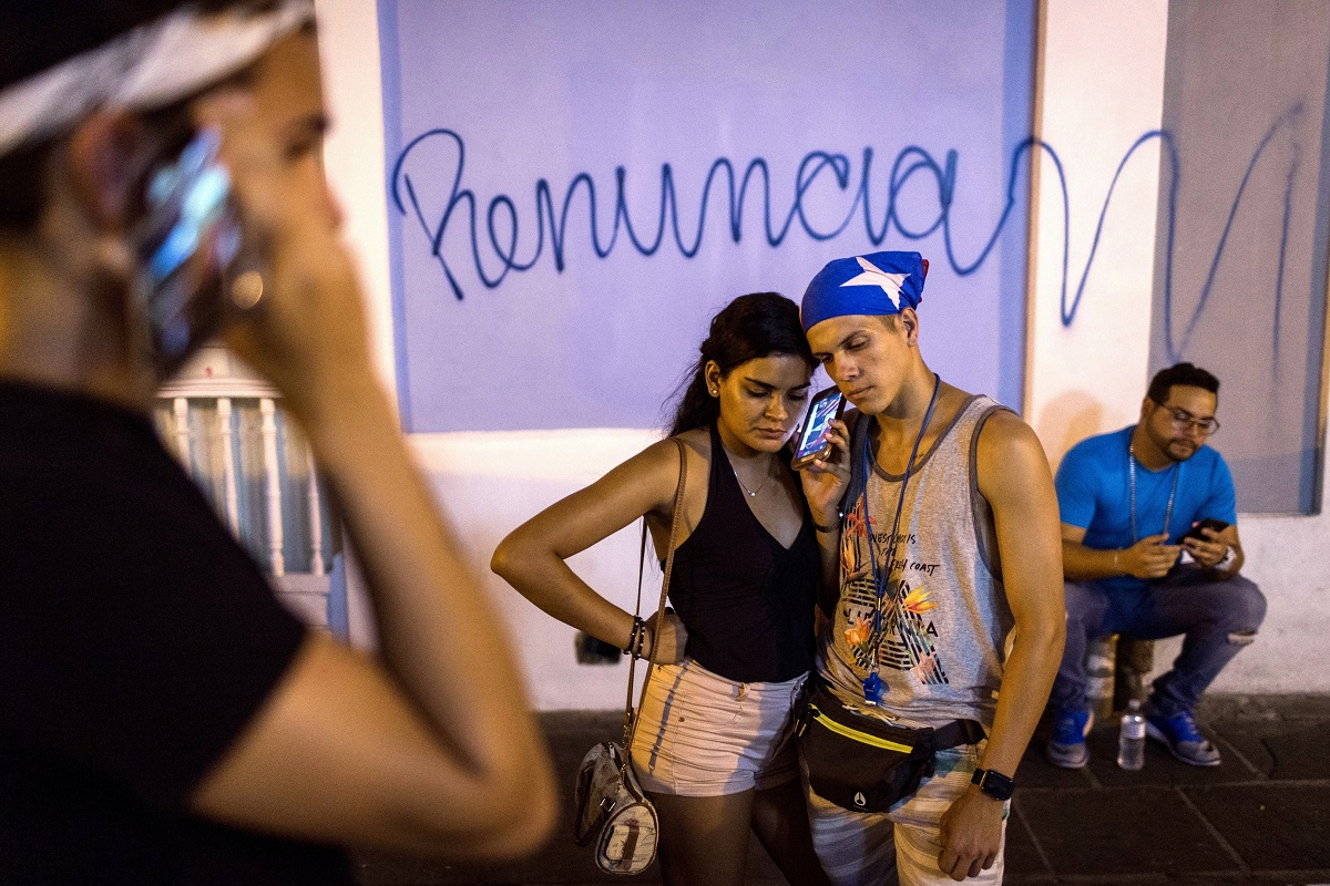 Locals listen on a smartphone to the pre-recorded message by Puerto Rico Gov. Ricardo Rossello announcing that he is resigning August 2 after weeks of protests over leaked obscene, misogynistic online chats, in San Juan, Puerto Rico. (AP Photo/Dennis M. Rivera Pichardo)
