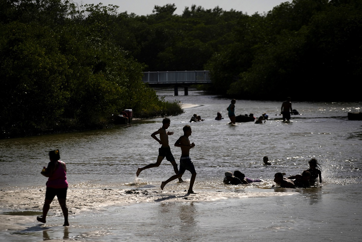 Youths race into the mouth of a river to cool off, on the outskirts of Havana, Cuba. Each summer thousands of Cubans leave the big city and head to the coast and the countryside with their families and pets to find respite from the heat, and for a time put aside the tensions generated by the shortages of food and medicine that once again have become a serious daily problem for millions of Cubans. (AP Photo/Ramon Espinosa)