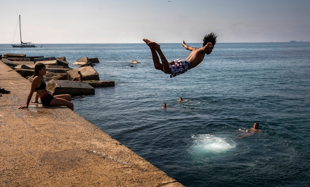 A boy jumps into the water at the beach in Barcelona, Spain. Europe saw record-high temperatures as much of the continent was trapped in a heatwave, the second in two months. (AP Photo/Emilio Morenatti)