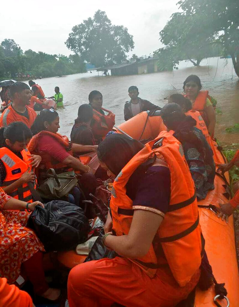 Passengers of the stranded Mahalaxmi Express on a rescue boat in floodwaters in Badlapur, Maharashtra, Saturday, July 27, 2019. (National Disaster Response Force via AP)