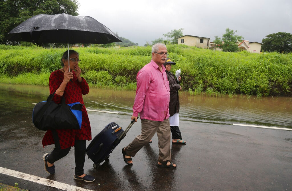 Passengers of the Mahalaxmi Express marooned in floodwaters, walk with their belongings after being rescued in Badlapur, India Saturday, July 27, 2019. (AP Photo/Rafiq Maqbool)
