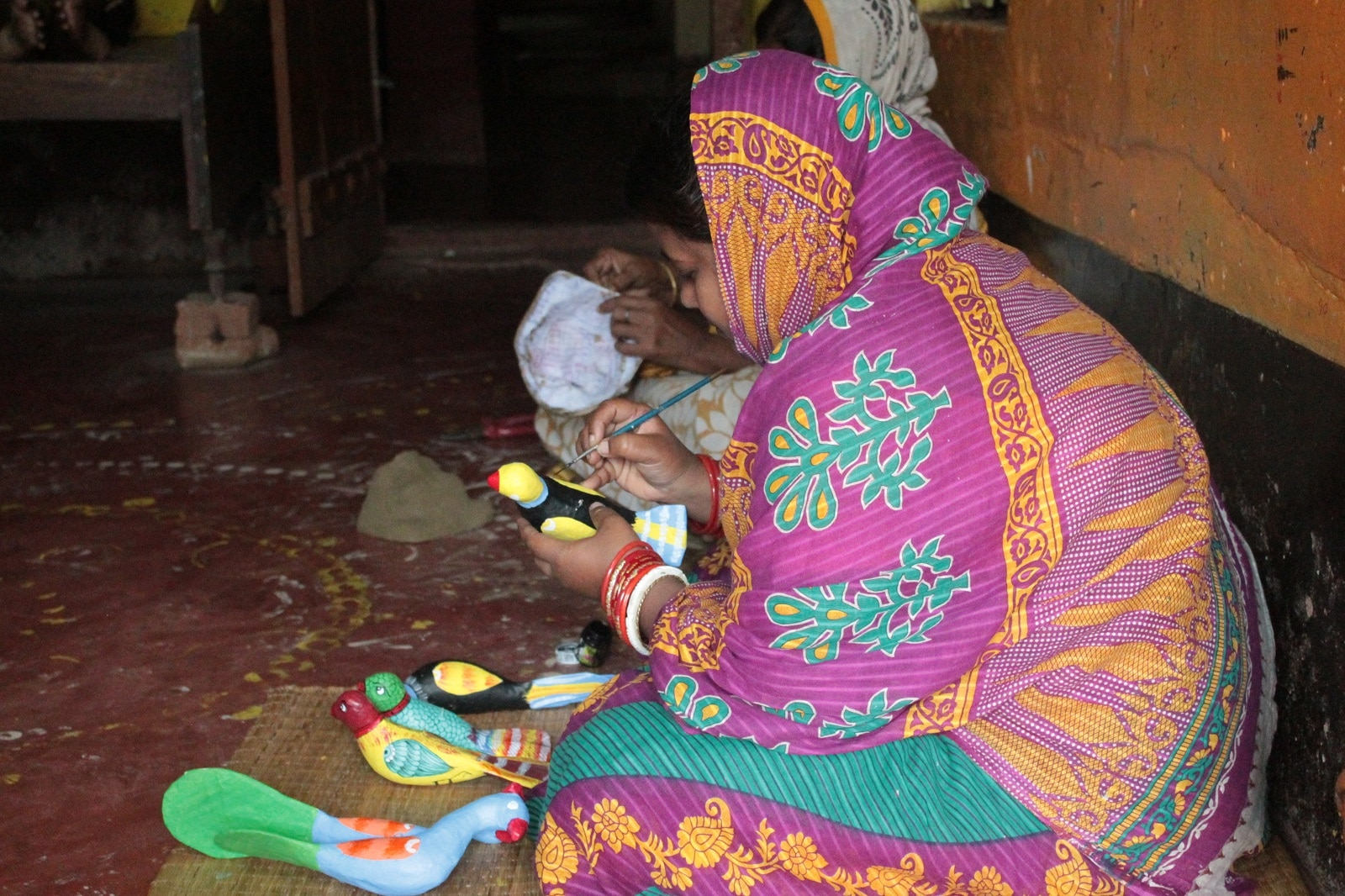 Women sit after finishing their household chores to paint dolls made out of cow dung and mud.