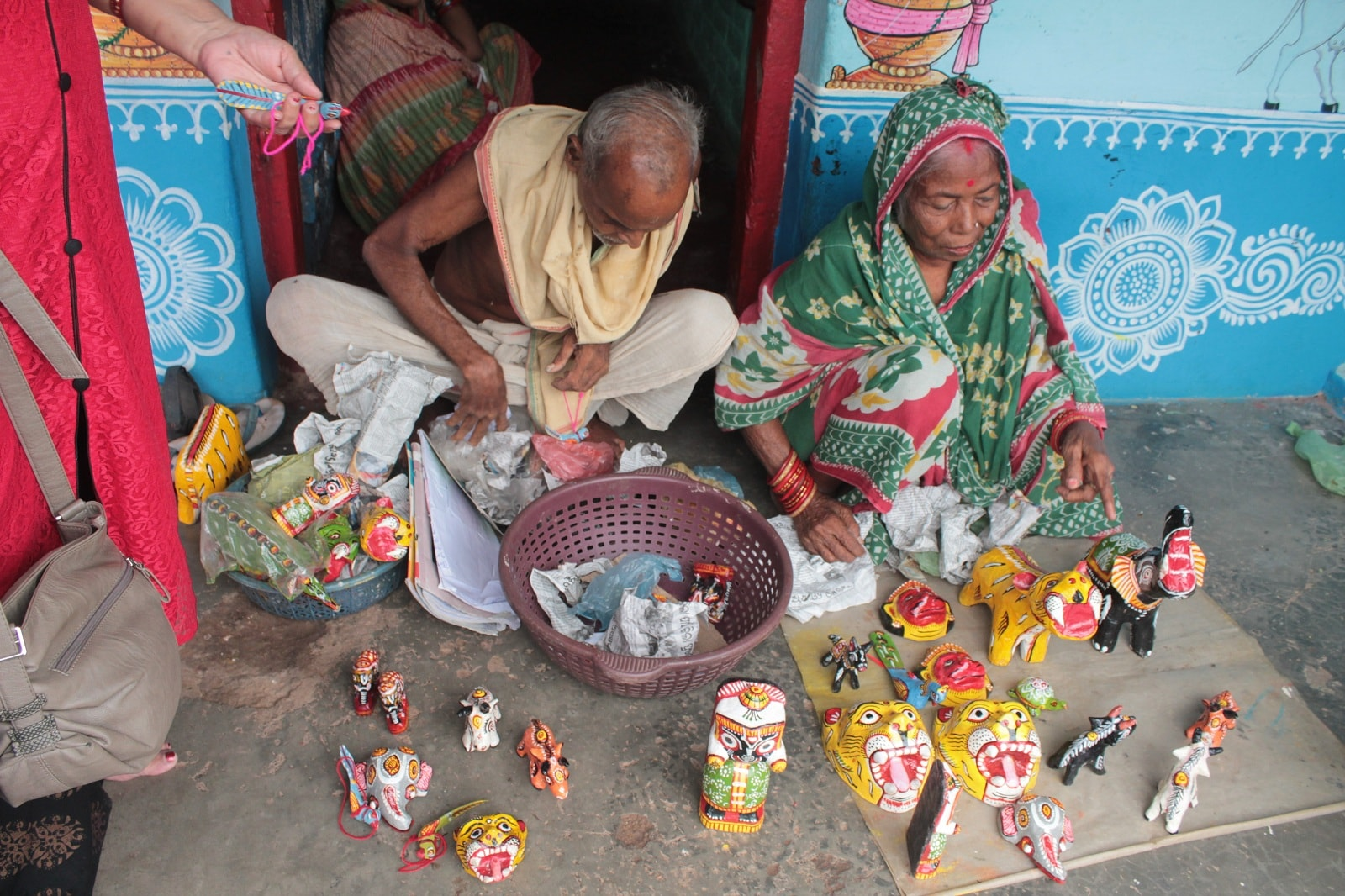 The elderly couple displays their work for customers, which includes paper masks and dolls.