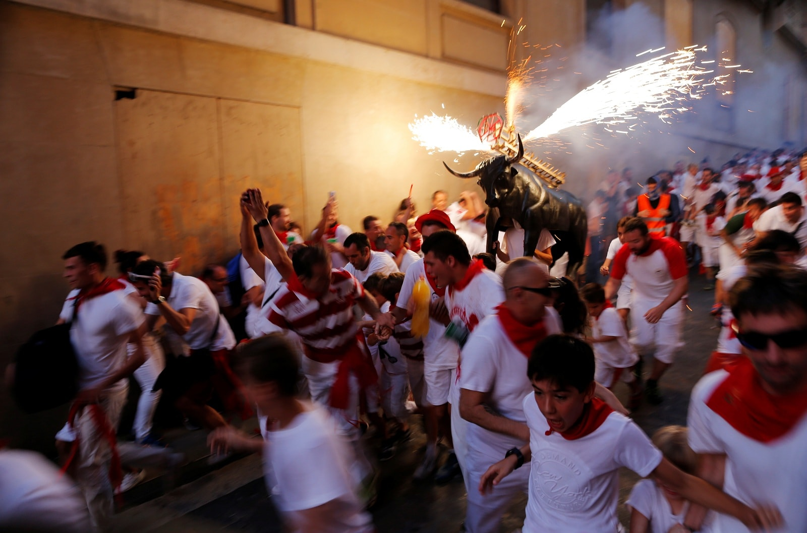 Revellers run next to the Fire Bull, a man carrying a bull figure packed with fireworks, during the San Fermin festival in Pamplona, Spain, July 7, 2019. REUTERS/Jon Nazca