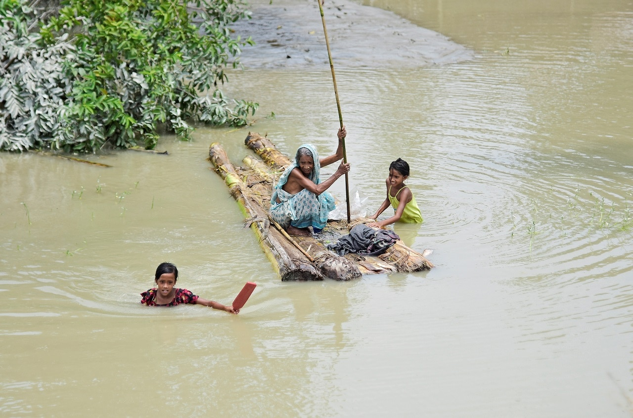 A woman rows a makeshift raft as girls wade through flood waters at the Laharighat village in Morigaon district, in Assam, July 21, 2019. REUTERS/Anuwar Hazarika