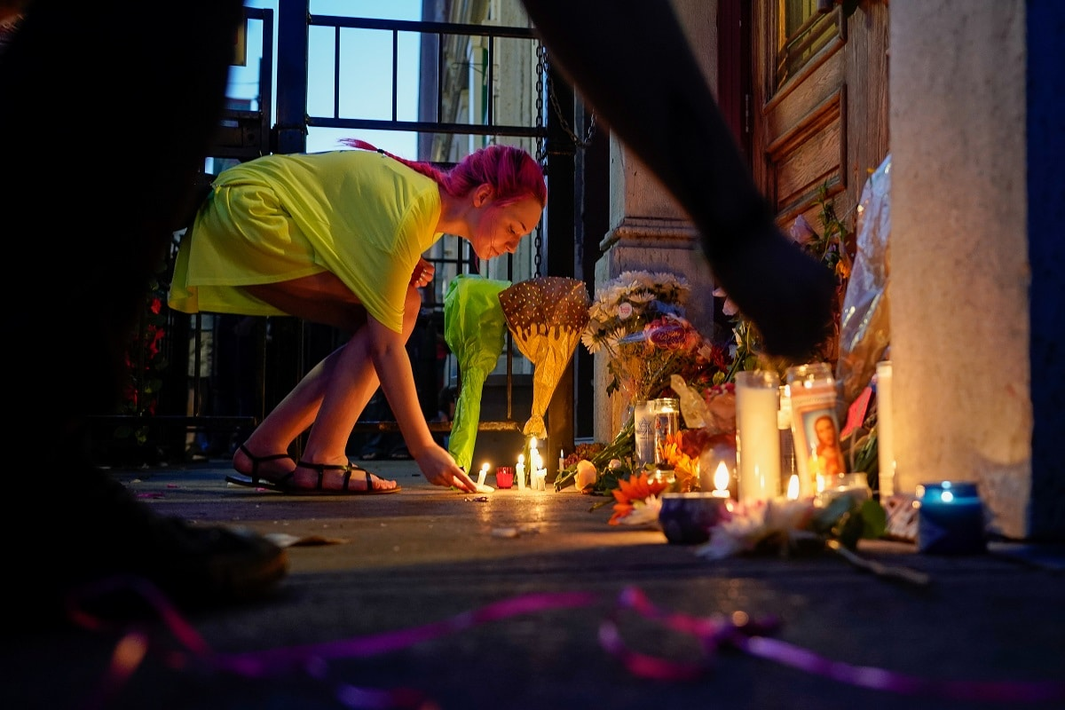 A mourner leaves a candle at the scene of a mass shooting in Dayton. REUTERS/Bryan Woolston