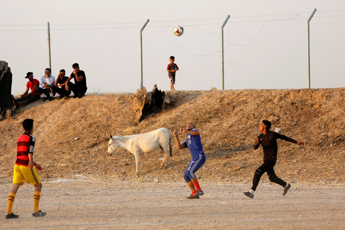Displaced Iraqi young boys, who return to camp after trying to go home and find the conditions in their towns unbearable, with lack of services and destroyed buildings, play football at Hassan Sham camp. Picture taken July 29, 2019. REUTERS/Abdullah Rashid