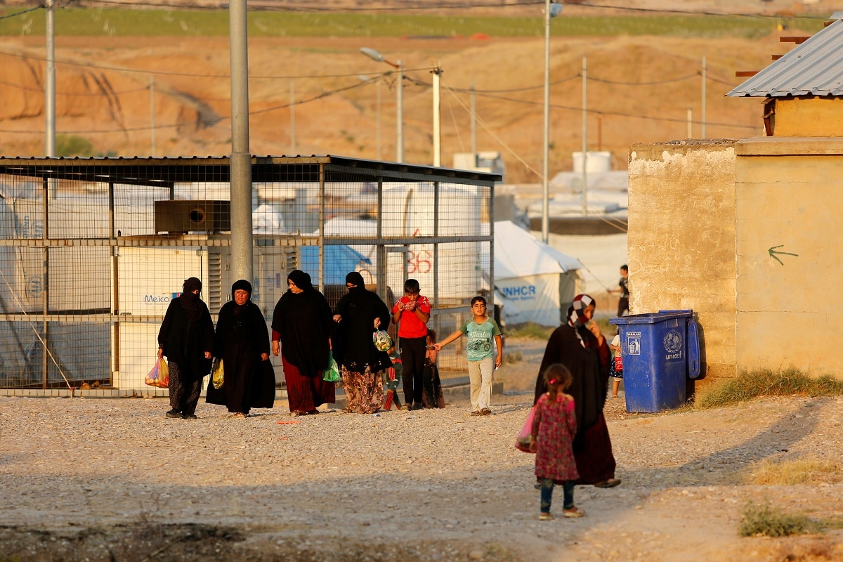 Displaced Iraqi women, who return to camp after trying to go home and find the conditions in their towns unbearable, with lack of services and destroyed buildings, are seen getting out from the bazaar at Hassan Sham camp. REUTERS/Abdullah Rashid