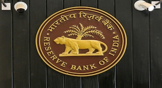 FILE PHOTO: CCTV cameras are seen installed above the logo of Reserve Bank of India (RBI) inside its headquarters in Mumbai
