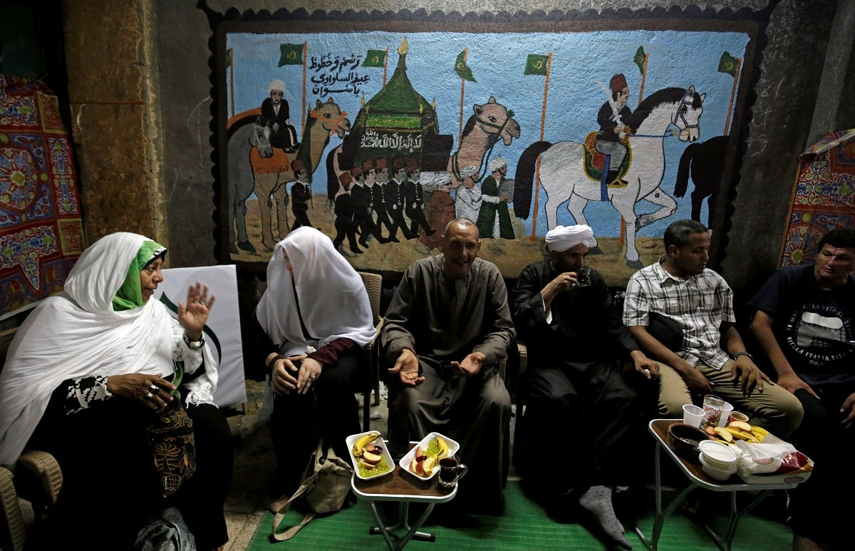 Men and women sit in front of murals painted by the artist Eid Al Salwaawi. REUTERS/Hayam Adel