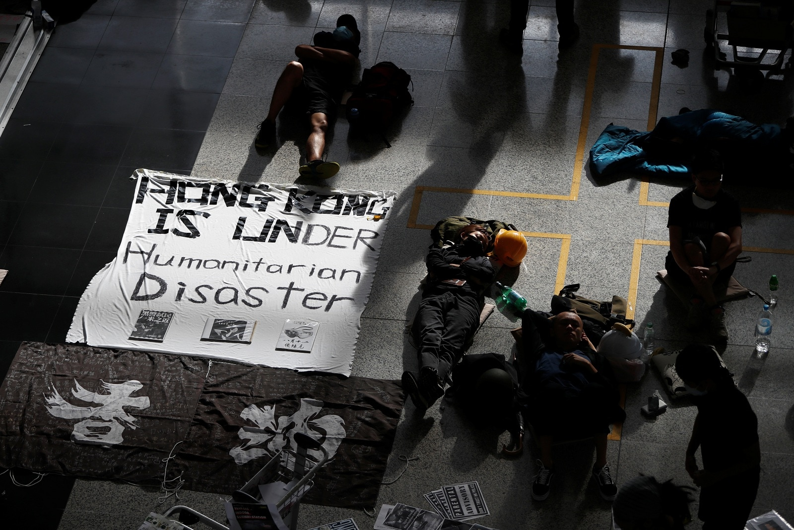 Some anti-extradition bill protesters rest on the floor a day after the airport was closed due to a protest, at Hong Kong International Airport, China August 13, 2019. REUTERS/Issei Kato