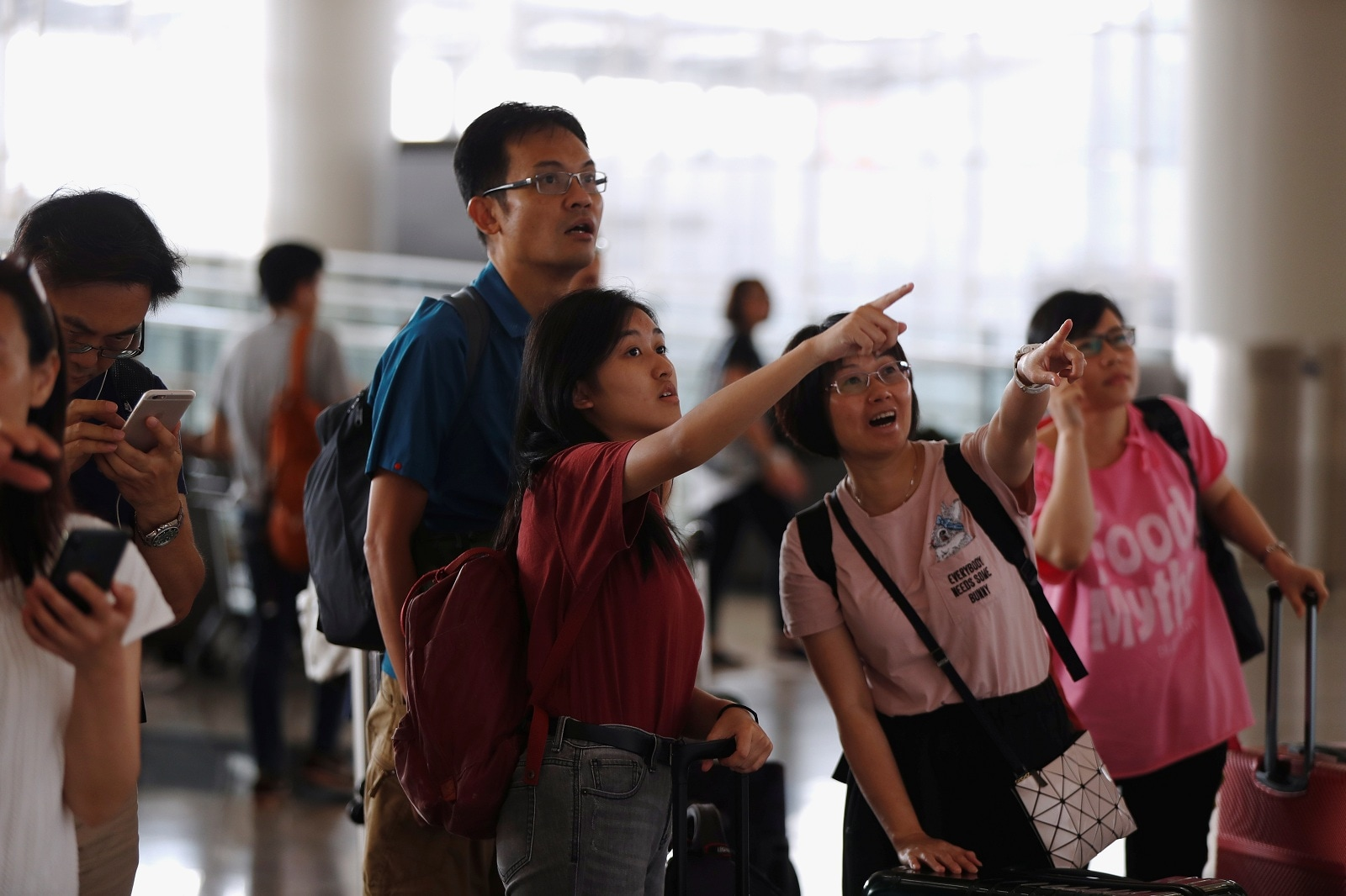 Passengers react as they check the flight information board a day after flights were halted due to a protest, at Hong Kong International Airport, China August 13, 2019. REUTERS/Issei Kato