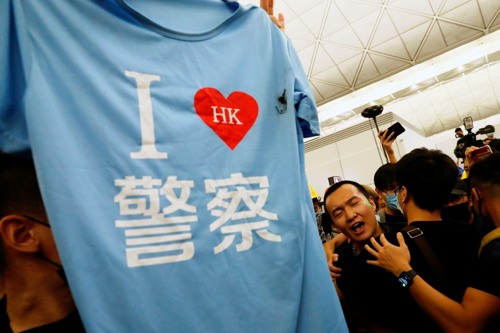 "A tee-shirt where it reads ""I love Hong Kong police"" is found in the bag of Fu Guohao (C), reporter of Chinese media Global Times website, during a mass demonstration at the Hong Kong international airport, in Hong Kong, China, August 13, 2019. REUTERS/Tyrone Siu"