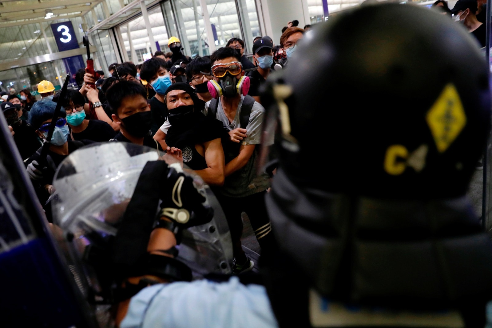 Anti-extradition bill protesters face riot police during a mass demonstration at the Hong Kong international airport, in Hong Kong, China, August 13, 2019. REUTERS/Tyrone Siu